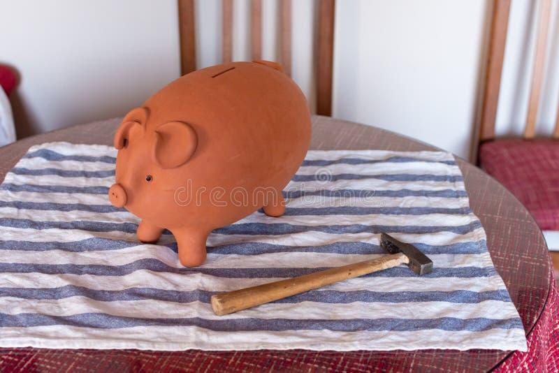 Prosiątko bank w formie brąz świni i młota na stole fotografia stock