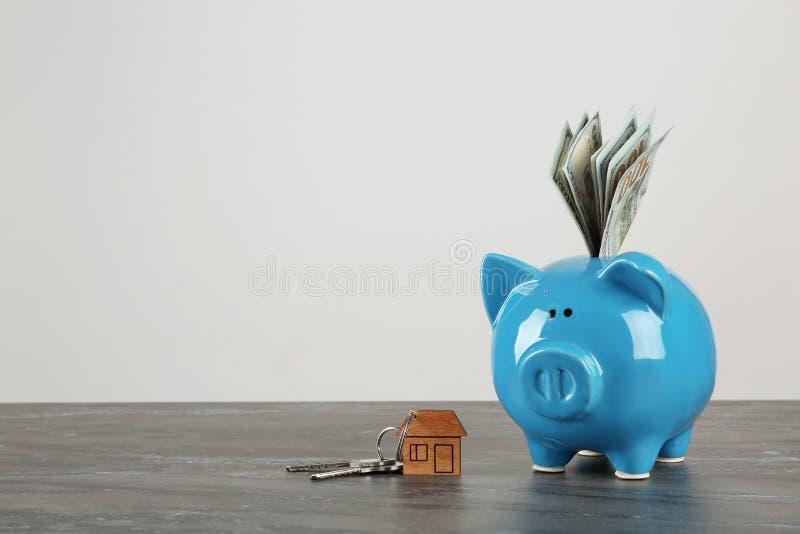 Prosiątko bank z dolarowymi banknotami i domów kluczami na stole przeciw białemu tłu zdjęcia stock