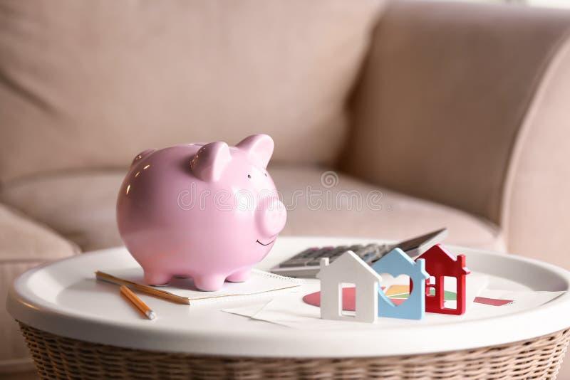 Prosiątko bank z domem modeluje na bielu stole koncepcja real nieruchomo?ci zdjęcie royalty free