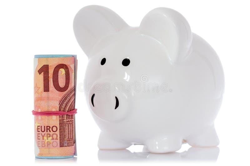 Prosiątko bank z pieniądze rolką obrazy royalty free