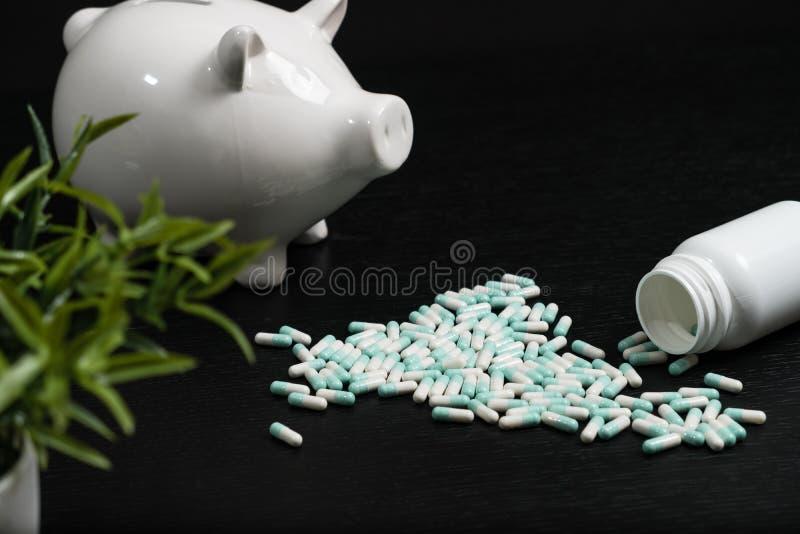 Prosiątko bank z pigułkami i monetami na białym tle obraz royalty free