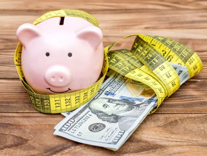 Prosiątko bank z pomiarową taśmą i pieniądze zdjęcie stock