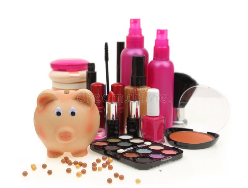 Prosiątko bank z różnorodnymi kosmetykami zdjęcia royalty free