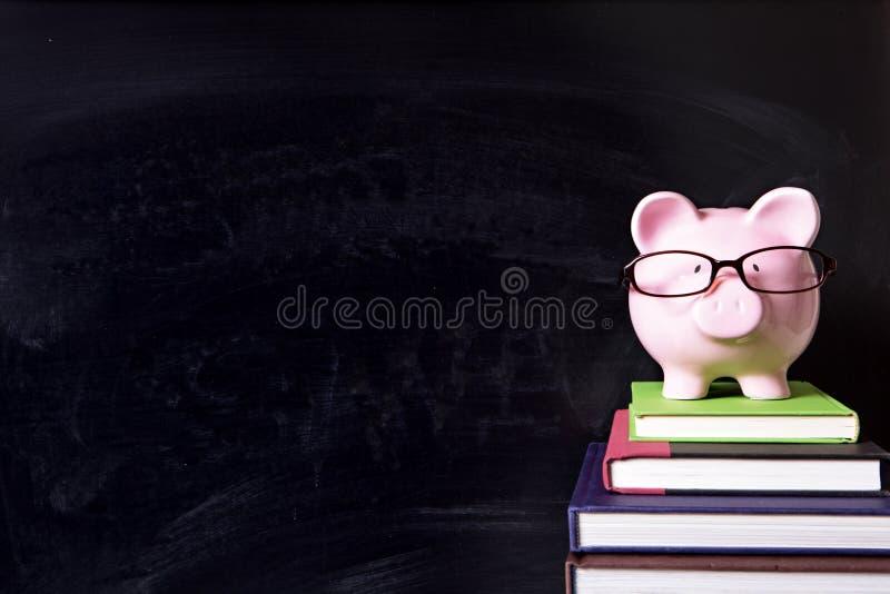 Prosiątko bank z szkłami i blackboard, szkoła wyższa funduszu pojęcie obraz stock