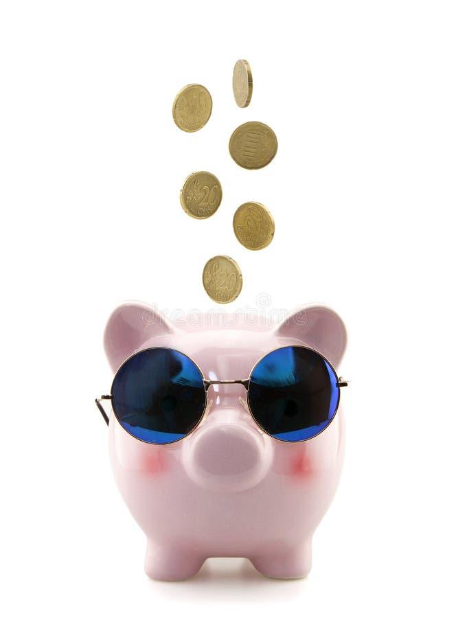 Prosiątko bank z szkłami i spada monetami zdjęcie stock