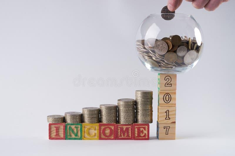 Prosiątko banka set na drewnianych blokach liczba 2017 z biznesmena ` s ręki kładzenia monetą w pieniądze słoju zdjęcie stock