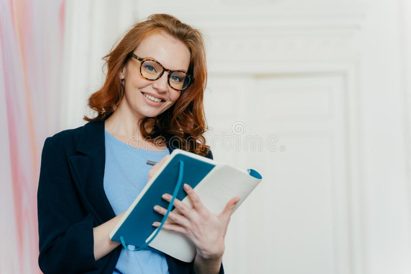 Prosperous satisfied businesswoman in elegant clothes writes in diary, has glad expression, wears spectacles, makes list of plans. Writes text message in royalty free stock photography