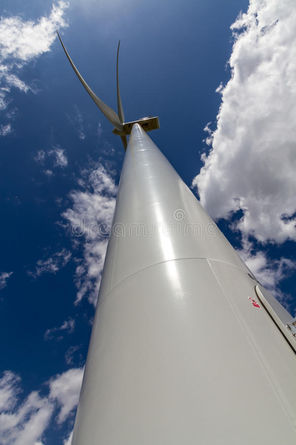 Prospettiva diritta-su rara del primo piano di Sunny Side di un generatore eolico industriale di alta tecnologia enorme che genera immagini stock libere da diritti