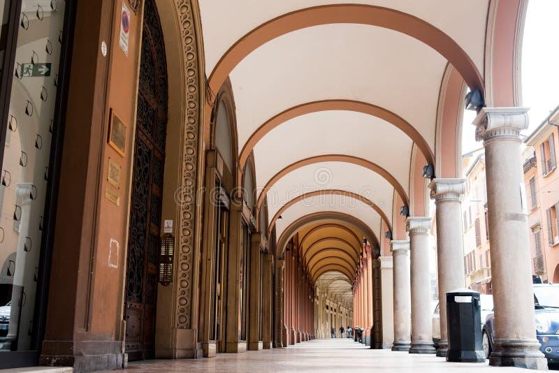 Prospettiva diversa dei portici di Bologna con le automobili e la gente che camminano durante il giorno di estate, di un punto di immagine stock libera da diritti
