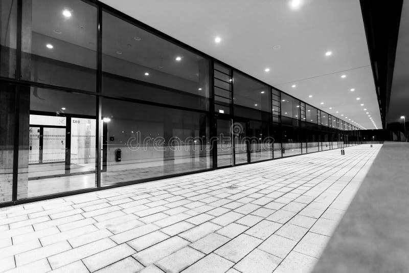 Prospettiva pedonale illuminata del passaggio lungo la facciata di costruzione di vetro fotografie stock