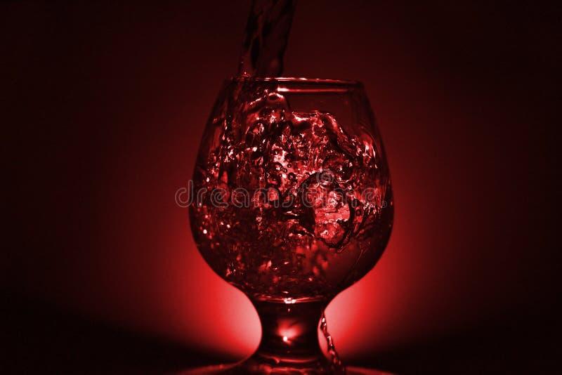 Prosta życie fotografia whisky szkło, wodny strumień l i ciemnawa czerwień, obraz royalty free