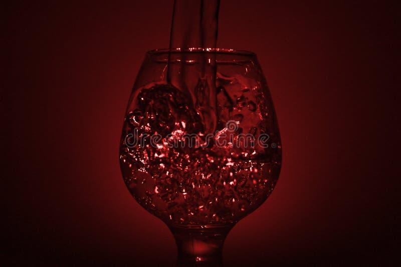 Prosta życie fotografia whisky szkło, wodny strumień l i ciemnawa czerwień, zdjęcia stock