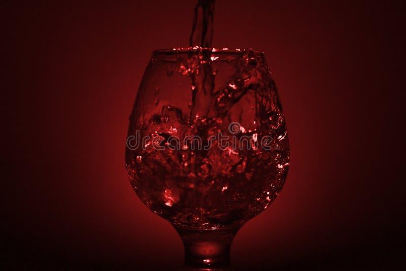 Prosta życie fotografia whisky szkło, wodny strumień l i ciemnawa czerwień, obrazy stock