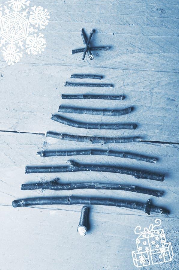 Prosta choinka układał od drewnianych kijów, driftwood drewniany zimy błękita tło obraz stock