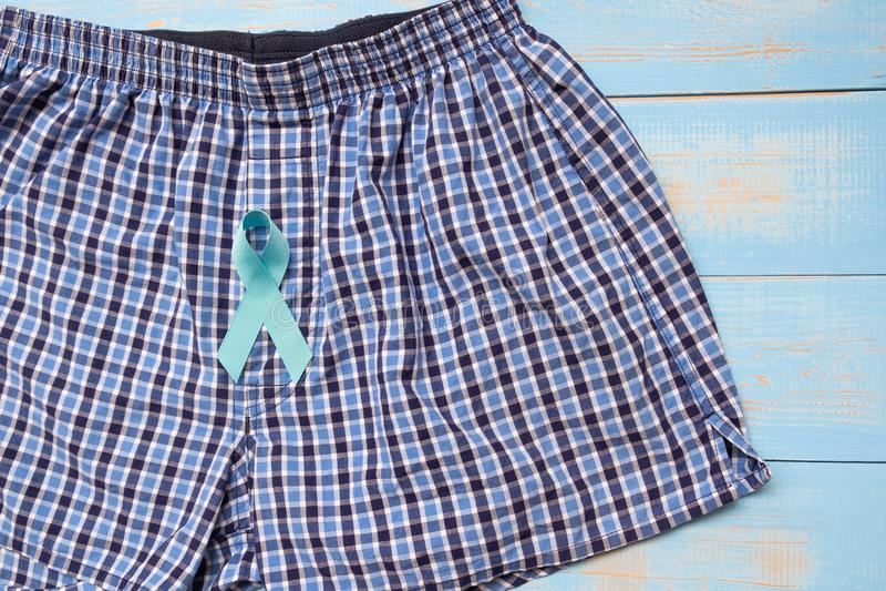 Prostatakrebs-Bewusstsein, hellblaues Band mit männlichen Unterhosen auf blauem hölzernem Hintergrund lizenzfreies stockfoto