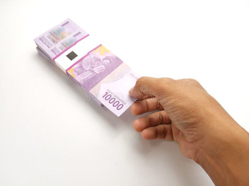 Proste zdjęcie: Koncepcja, widok z góry Kaukaz z prawej ręki, wybieranie arkusza 10000 Rupiah Indonesia Paper Money na biało obraz stock