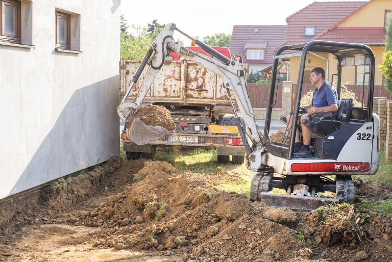 Prostejov tjecktekniker 19 6 2018 mini- grävskopa på konstruktionsplats Grävskopan reglerar terrängen runt om huset arkivbild