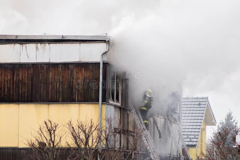Prostejov Tsjechisch die Rep achtentwintigste Januari - Brandweerlieden op een ladder in een venster in rook wordt behandeld Echt royalty-vrije stock fotografie