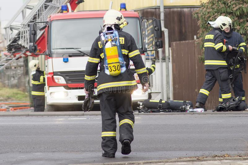 Prostejov Tsjechisch Rep achtentwintigste Januari - Brandweerman die naar een firetruck lopen tijdens echte brandbestrijdingsacti royalty-vrije stock foto
