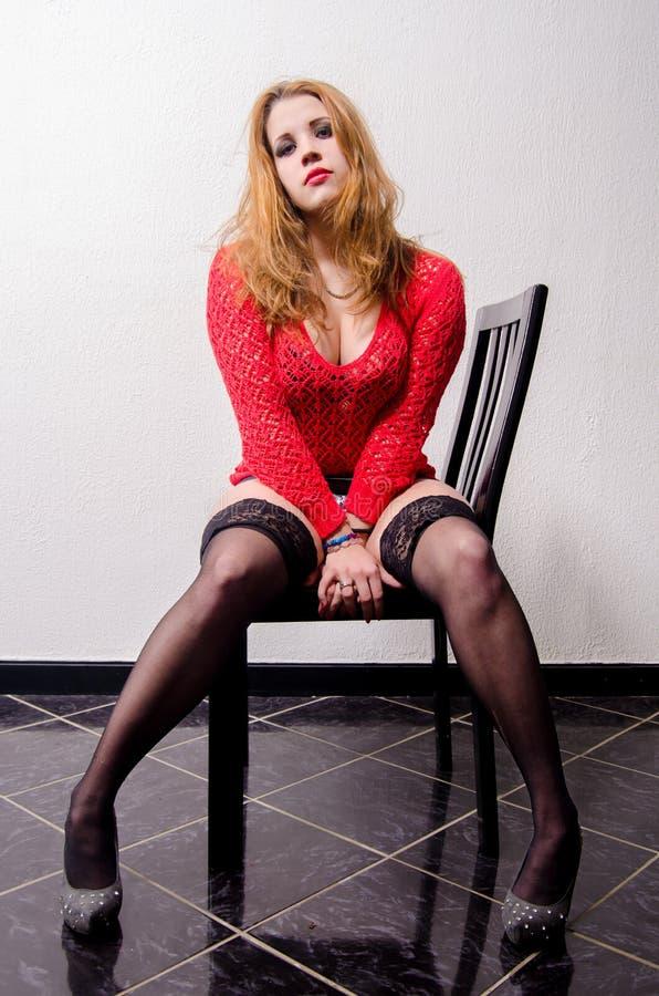 Prostituera i rött tröja- och halterssammanträde som till hälften är naket på stolen royaltyfri foto