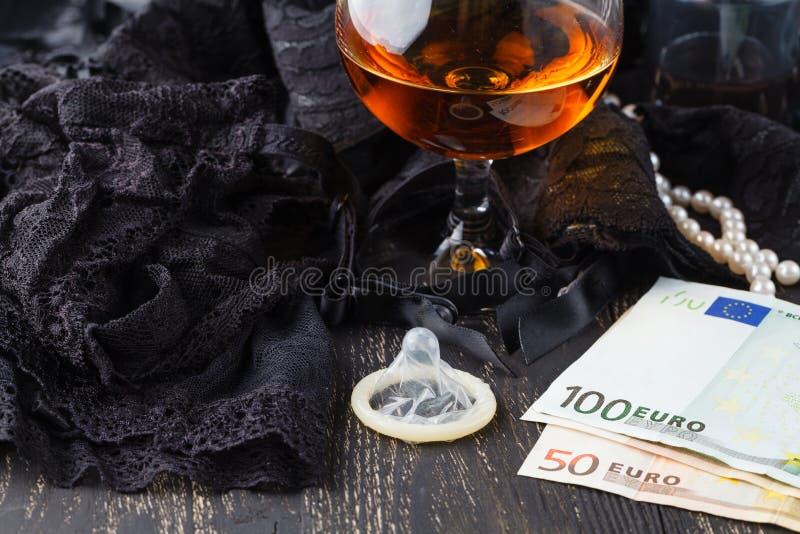 Prostituierte oder Stripteasekonzept, Eurobanknote mit sexy Spitzeen und Kondom lizenzfreie stockfotos