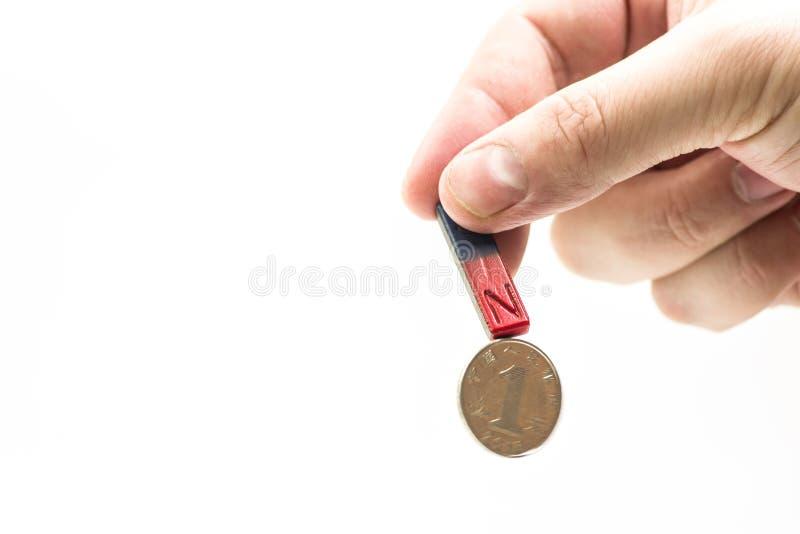 Prostokąta magnes w męskiej ` s ręce przyciąga monety obrazy stock