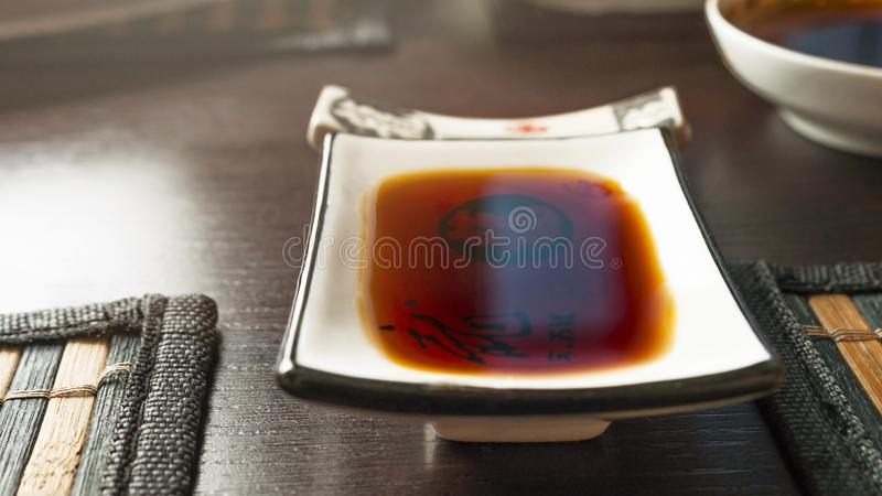 Prostokątny soja kumberlandu maczania naczynie na zmroku stole z bambusem Łomota maty Chopstick odpoczynek, puchar w Zamazanym tl zdjęcie stock