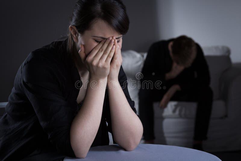 Prostrate哭泣的妇女和人 免版税库存图片