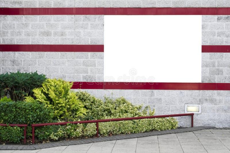Prosty biały sztandar na dekoracyjnej ścianie z zielonymi krzakami i czerwień lampasami zdjęcie royalty free
