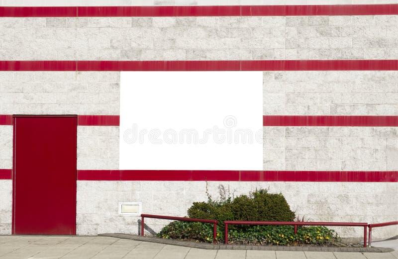 Prosty biały sztandar na dekoracyjnej ścianie z zielonymi krzakami i czerwień lampasami fotografia stock