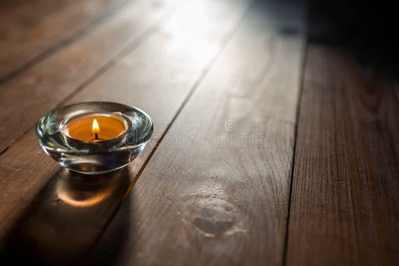 Prosty Bożenarodzeniowy tło wizerunek, płonąca świeczka na drewnianym tle, wchodzić do naturalne światło obraz stock