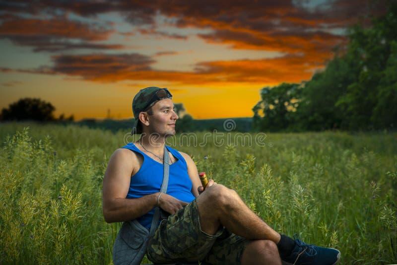 Prosty facet w nakrętce cieszy się naturę i cisza z butelką wino, w tle jest pięknym lata zmierzchem zdjęcie royalty free