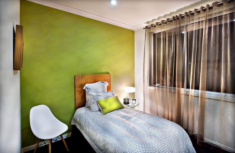 Prosty i mały łóżko iluminujący stołową lampą obraz stock