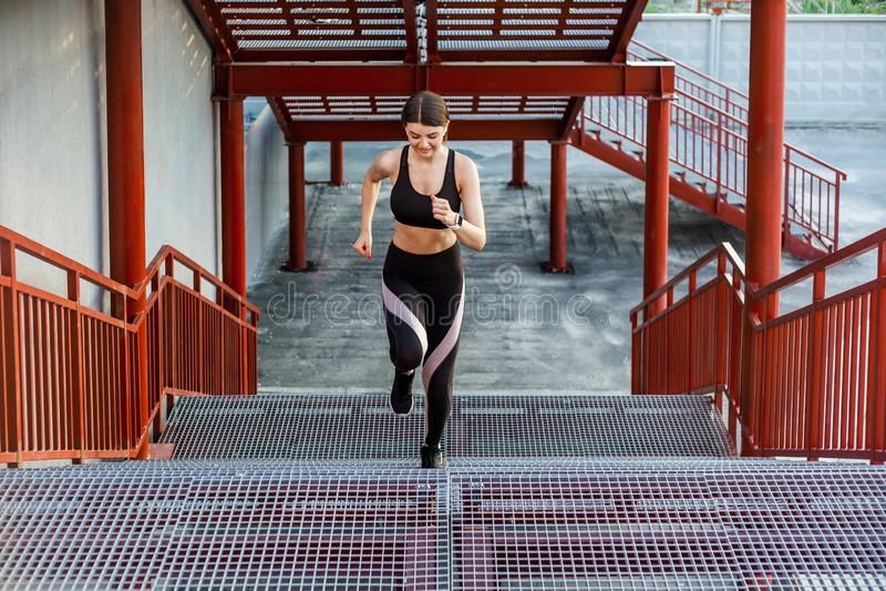 Prosty widok młoda sportowa szczupła piękna kobieta działająca w górę schodków robi cardio interwału szkoleniu w czarny modnym obraz royalty free