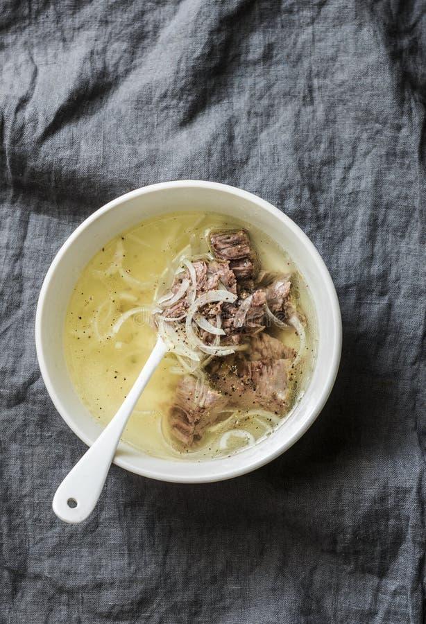 Prosty wołowina rosół z mięsem, cebulą i pieprzem na popielatym tle wołowiny, Zdrowy jedzenie, zupna baza obraz stock