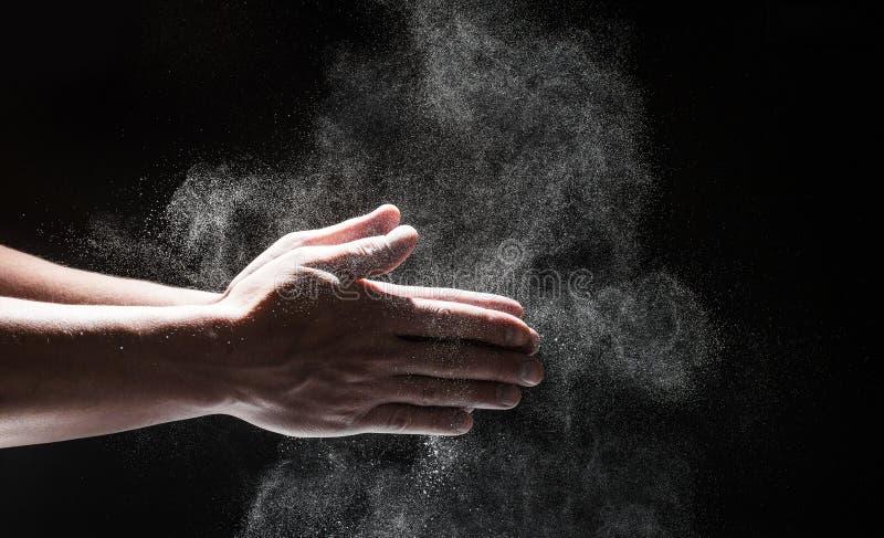 Proszkowaty mąki latanie w powietrze jako mężczyzna w czarnym szefa kuchni stroju wyciera daleko jego ręki obrazy royalty free