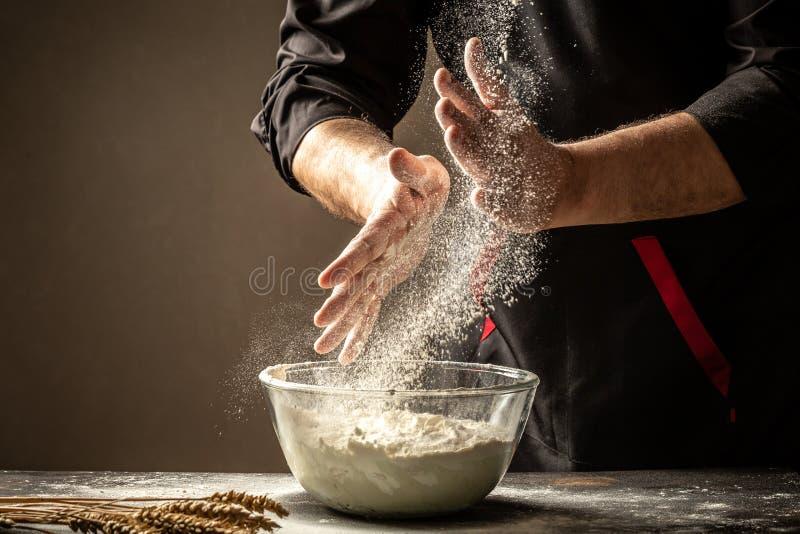 Proszkowaty mąki latanie w powietrze jako mężczyzna w czarnym szefie kuchni oddaje stołowego zakrywającego w mące strój wyciera j obraz stock