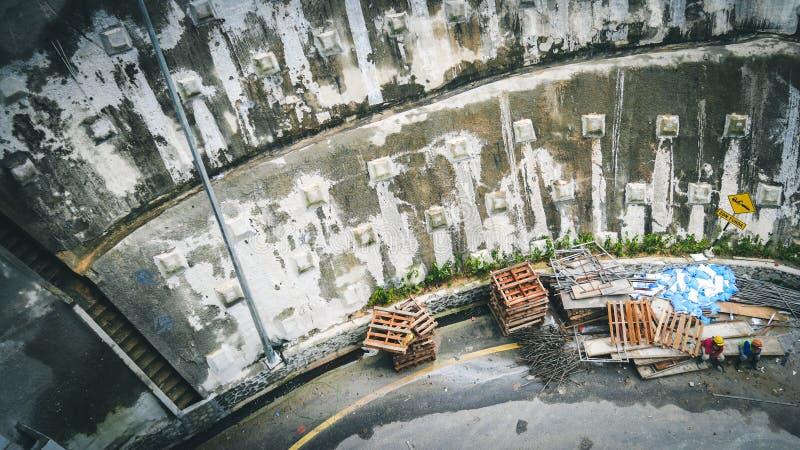 Proteção concreta da parede de Gabion da rua da montanha da corrediça rochosa do tálus ou da terra na estrada com o trabalhador d fotografia de stock