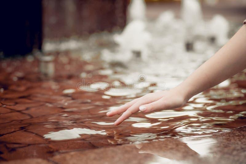 Proteção da água fresca na terra desidrata??o O dedo ascendente próximo toca na água e na gota da água que caem e que criam fotografia de stock