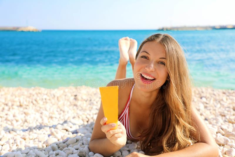 Proteção de sorriso do tubo do creme do sol da terra arrendada da mulher que encontra-se na praia dos seixos Menina da proteção s imagem de stock royalty free