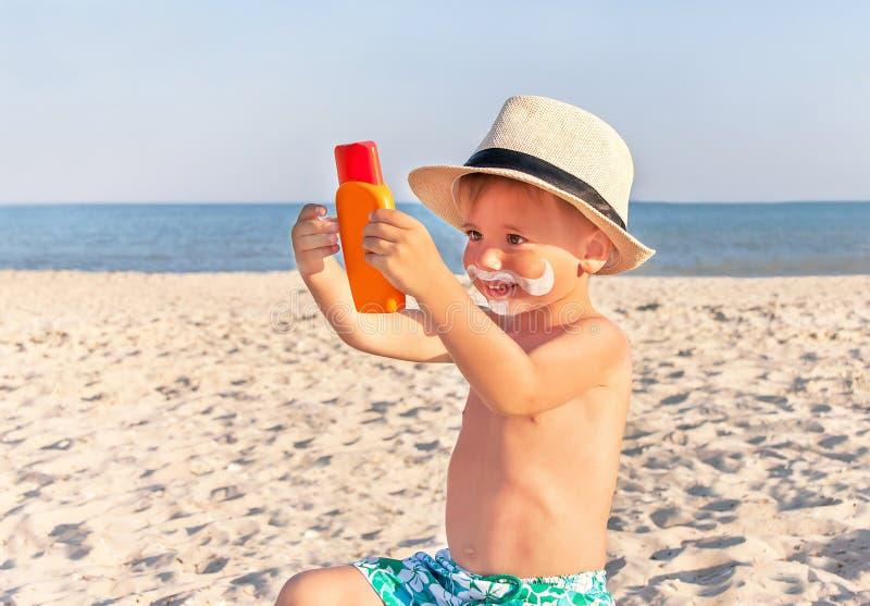 A proteção solar do desenho do bigode na cara do bebê (menino) fotografia de stock