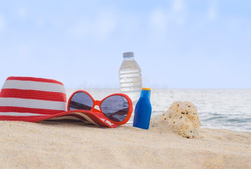 A proteção solar, o chapéu, os óculos de sol e a garrafa da água na areia encalham fotografia de stock royalty free