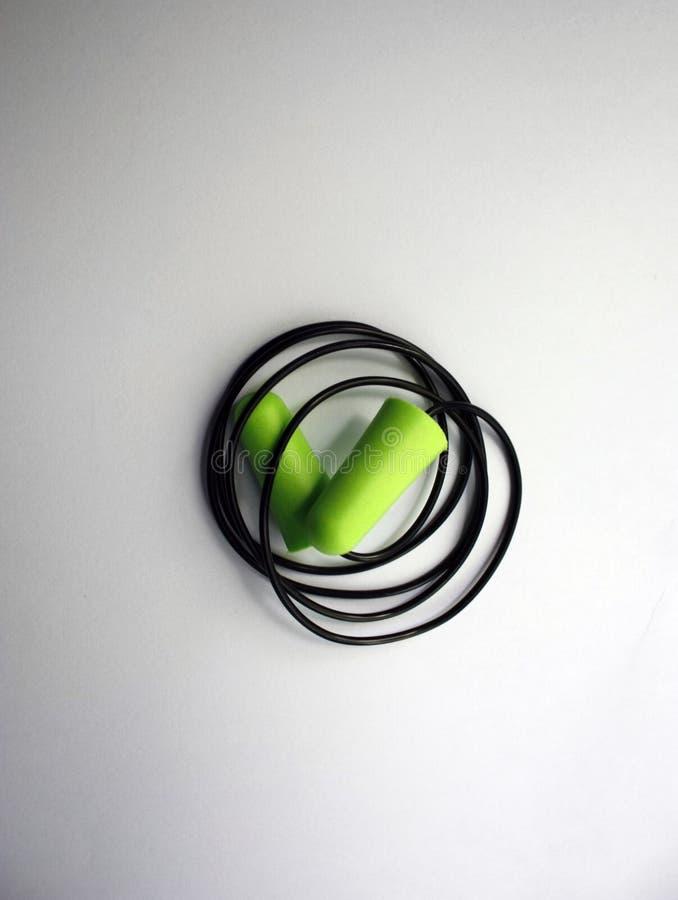Proteção verde do ruído do tampão de ouvido para a segurança ocupacional em um fundo branco Close-up imagem de stock royalty free