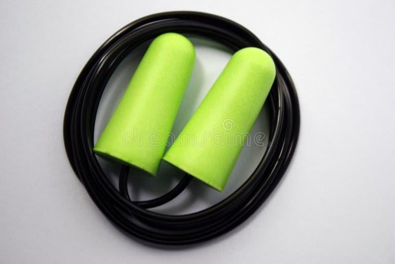 Proteção verde do ruído do tampão de ouvido para a segurança ocupacional em um fundo branco Close-up foto de stock