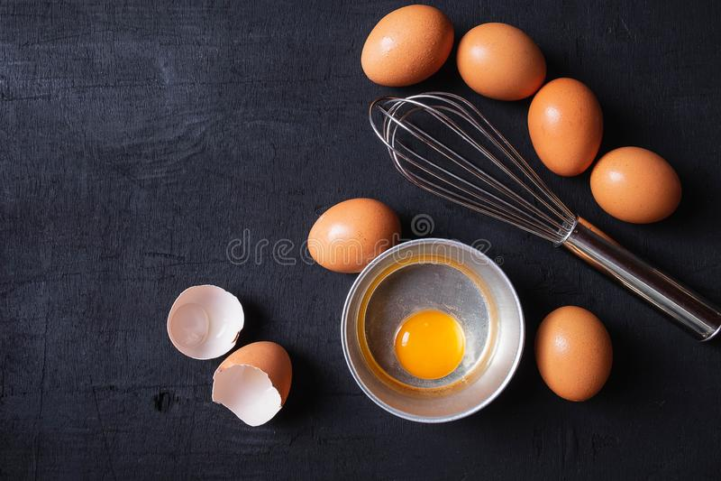 Proteína de las yemas de huevo y del huevo en una taza Huevos del batidor de Corolla preparación imagen de archivo