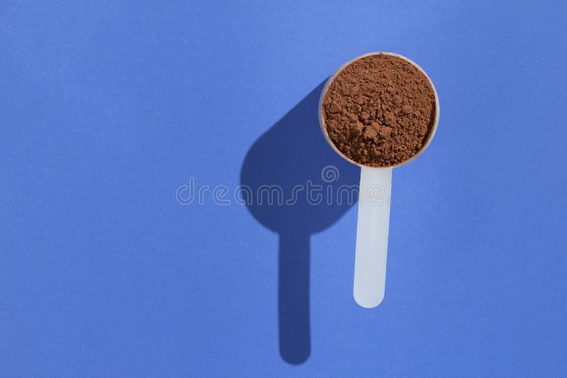 Proteína do soro Conceito mínimo e luz dura Colher com chocola fotos de stock royalty free