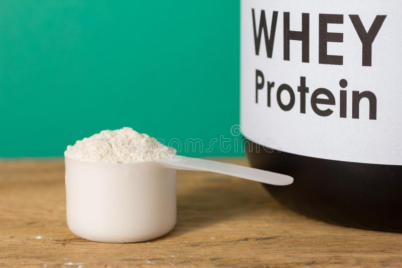 Proteína do soro Vista dianteira da colher com pó e frasco da baunilha sobre fotos de stock