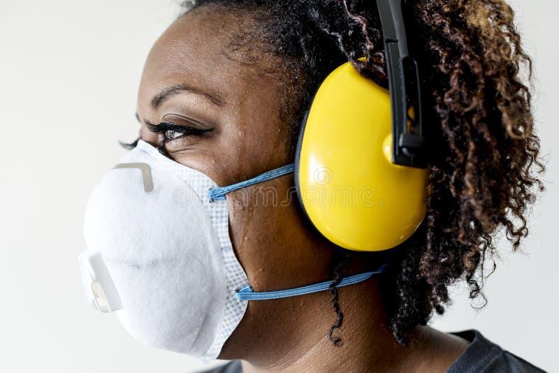 Protección auditiva de la mujer que lleva negra imagen de archivo libre de regalías