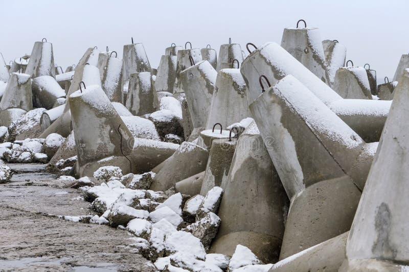 Protección costera concreta en la nieve, rompeolas concretos en invierno imagenes de archivo