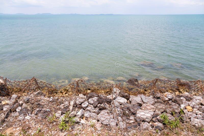 Protección costera, ondas que se rompen en un rompeolas rocoso en la playa en Koh Chang, Tailandia foto de archivo libre de regalías